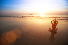 Silhouette yoga woman sitting on sea coast at sunset. Nature. Royalty Free Stock Images