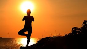 Yoga at sunset. Silhouette Yoga with young woman on sunset stock video footage
