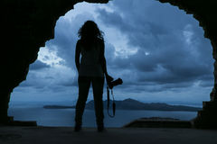 Silhouette of a youn woman holding a camera on the rock by the s Royalty Free Stock Image