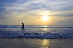 Young active woman on sea landscape sunset horizon with amazing sun and dramatic orange sky Royalty Free Stock Photography