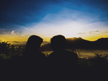 Silhouette young asian couple 25s to 35s see face eye contact. Together from travel and see sunrise from mountain at north east of thailand Stock Image