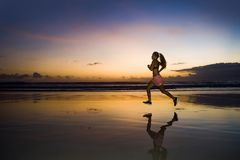 Silhouette of young Asian sport runner woman in running workout stock photography