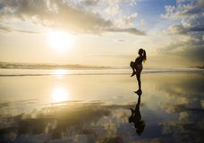 Silhouette of young attractive Asian woman stretching leg in war. M up before running workout in sunset beach with amazing beautiful sunlight reflection on sand royalty free stock image