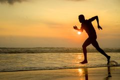 Silhouette of young attractive fit athletic and strong black African American man running at sunset beach training hard and stock photography