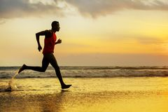 Silhouette of young attractive fit athletic and strong black African American man running at sunset beach training hard and stock image