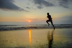 Silhouette of young attractive fit athletic and strong black afro American man running at sunset beach training hard and sprinting royalty free stock photos