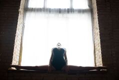 Silhouette of a young, flexible well shaped ballerina sitting on the huge window