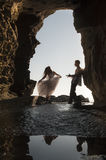 Silhouette young beautiful bridal couple in rock archway at beach. Young beautiful bridal couple dancing in rock archway at beach Stock Photo