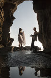 Silhouette young beautiful bridal couple in rock archway at beach. Young beautiful bridal couple dancing in rock archway at beach Royalty Free Stock Images