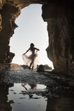 Silhouette young beautiful bride in rock archway at beach. Silhouette young beautiful bride dancing in rock archway at beach Stock Image