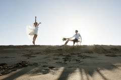 Silhouette of young beautiful couple hanging out together at the beach Stock Image