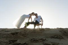 Silhouette of young beautiful couple hanging out together at the beach Stock Photo