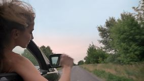 Silhouette of young beautiful girl puts head and hand out of car window during ride, trevel concept.  stock footage