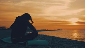 Silhouette of young beautiful healthy woman meditating in lotus position by the sea at sunset. Young woman practicing stock video footage