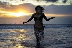 Silhouette of young beautiful and sexy asian woman running free and happy having fun at sunset beach in Bali Stock Image