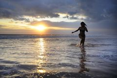 Silhouette of young beautiful and sexy asian woman running free and happy having fun at sunset beach in Bali Stock Photography