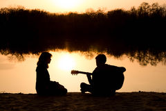 Silhouette of a young boy and girl on the beach with a guitar Stock Photo