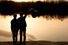 Silhouette of a young boy and girl with a guitar Royalty Free Stock Photography