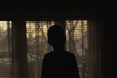 Silhouette of young boy in house stock images