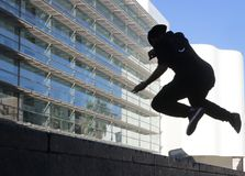 Silhouette of young boy jumping in barcelona. Silhouette of young boy jumping next to museum of modern arts of barcelona MACBA facade Royalty Free Stock Photos