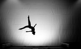 Silhouette of young boy jumping on trampoline. Indoor Stock Image