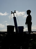 Silhouette of young boy in Langa. Silhouette of a young boy gathering water at a well in Langa, South Africa, a township located on the outskirts of Cape Town royalty free stock photography
