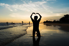 Silhouette of young boy making heart sign with his arms on the b Stock Image