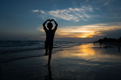 Silhouette of young boy making heart sign with his arms on the b Royalty Free Stock Photo