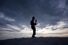 Silhouette of young boy performing a pencak silat Royalty Free Stock Images