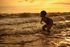 Silhouette of young boy playing crazy happy and free at the beach splashing with water playing with sea waves jumping and having stock photos