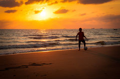 Silhouette of young boy playing a football on the beach in sunse Stock Images
