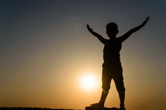 Silhouette of Young Boy Standing with Open Arms Stock Images