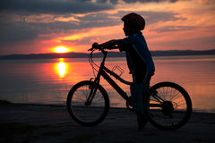 Silhouette of a young boy, at sunset, riding bicycle Royalty Free Stock Photo