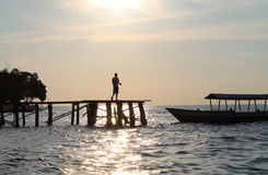 Silhouette of young boy on wooden walkway to the Bajau Village. Togean island, Indonesia Royalty Free Stock Photography