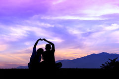 Silhouette young brother and sister made a heart shape, Beautifu Stock Photography