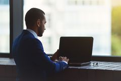 Silhouette of young business man sitting near big office window. Typing on laptop Stock Image