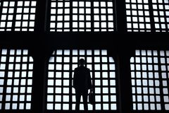 Silhouette of young businessman is standing in office with panoramic windows. royalty free stock photos