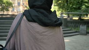 Silhouette of young calm muslim girl in hijab walks up stairs in park in daytime in summer, religious concept, urban. Concept stock video footage