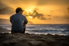 Silhouette of young caucasian male sitting on Sunset Beach looking out at sunset over the ocean stock photo