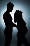 Silhouette of a young couple expecting a baby. Studio photo Royalty Free Stock Photo