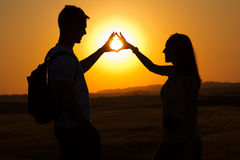 Silhouette of young couple in field. Royalty Free Stock Photo