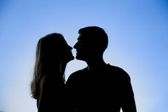 Silhouette of a young couple kissing. On blue sky Royalty Free Stock Image