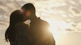 Silhouette of a young couple in love on the background of sky and sun, looking at each other stock video footage