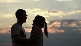 Silhouette of a young couple in love at sunset. Boy kisses and hugs his girlfriend on the shore of the lake stock video