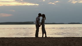 Silhouette of a young couple in love at sunset. Girl stood on tiptoe and gently kisses the guy on the shore of the lake stock video