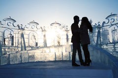 Silhouette of young couple near ice wall with sculptures Stock Photo