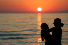 Silhouette of young couple at the sea Stock Photography