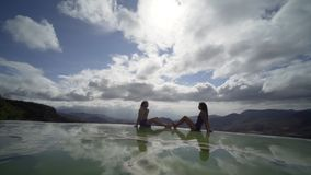 Mexico Hierve el Agua;. Silhouette of young couple siting on the beautiful view in mineral pool,figure reflecting in water, Mexico Hierve el Agua stock video