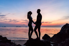 Silhouette young couple standing on the beach holding hands Royalty Free Stock Photography