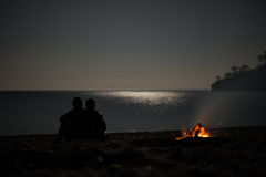 Silhouette of a young couple on summer beach near campfire at mo Stock Photography